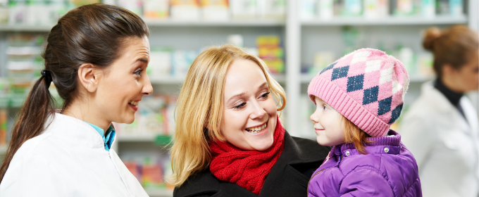 Pharmacist advising mother with baby