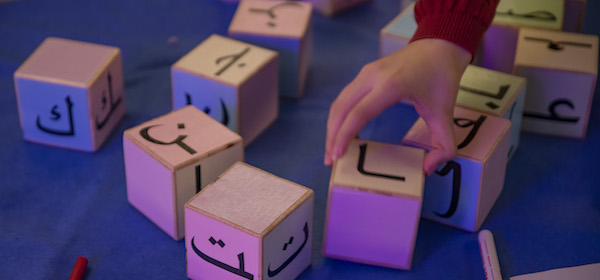 A child playing with language blocs to show language diversity