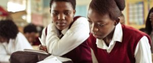 Two girls study a textbook in a rural African school.