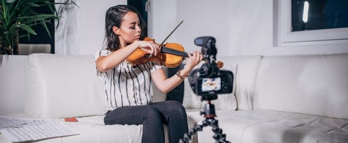 woman playing violin in front of camera